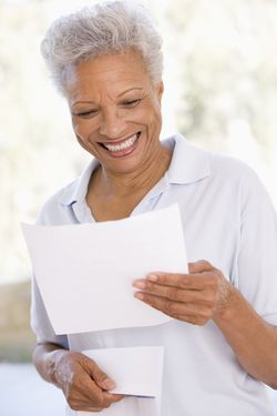 Bigstock-Woman-Reading-Letter-Smiling-4717981