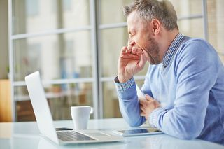 Bigstock-Tired-man-yawning-at-workplace-82977326